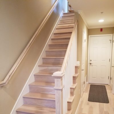 Los Altos residential: 15-tread stair and hand-railing assembly set, custom-stained to meet factory-finished front door entry flooring.